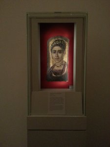 "View of ""Young Woman with Gilded Wreath"" in Vitrine, Egypt, Roman Period (120–140 CE, encaustic with gold leaf on wood , 14⅜ x 7 in [36.5 x 17.8 cm]).  The Metropolitan Museum of Art, New York.  Photo © Deborah Feller."